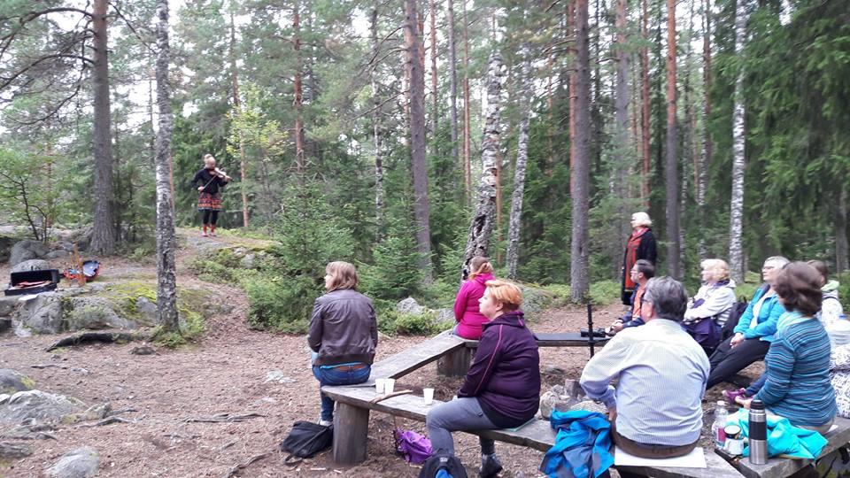 Yleisö nautiskelee konsertista metsän keskellä